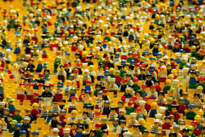 Hundreds of different lego figurines sitting in rows of stadium chairs.