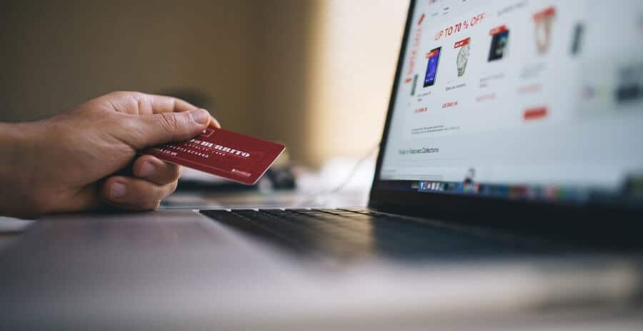 A person holding a credit card while looking on online shopping sales on a laptop